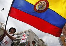 """Um colombiano segura uma bandeira do país na Avenida Central em Bogotá durante uma marcha pelas vítimas da guerra em Bogotá. A Fitch Ratings elevou o rating de crédito soberano em moeda estrangeira da Colômbia para """"BBB"""", ante """"BBB-"""", citando a melhora da dinâmica de dívida e políticas """"de credibilidade e consistentes"""". 09/04/2013 REUTERS/John Vizcaino"""