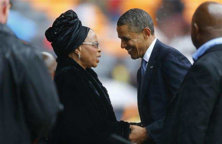 U.S. President Barack Obama (2nd R) pays his respect to former South African President Nelson Mandela's widow Graca Machel (2nd L) after his speech at the memorial service for late South African President Nelson Mandela at the First National Bank stadium, also known as Soccer City, in Johannesburg December 10, 2013. REUTERS/Kai Pfaffenbach