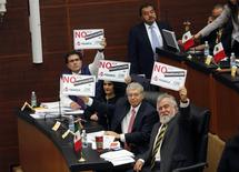 """Senadores del Partido de la Revolución Democrática sostienen afiches que rezan """"No a la privatización de Pemex"""" antes de comenzar un debate sobre una reforma energética en Ciudad de México, dic 9 2013. Tres comisiones de senadores mexicanos votarían el lunes en lo general un proyecto de reforma energética que facilitaría la inversión privada en la reservada industria de los hidrocarburos, en lo que sería la mayor apertura en décadas del estratégico sector. REUTERS/Henry Romero"""