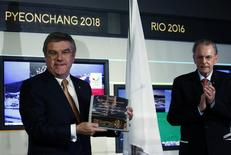 International Olympic Committee (IOC) President Thomas Bach (L) poses with the presidency key next to his predecessor Jacques Rogge during a ceremony at the Olympic Museum in Lausanne December 10, 2013. REUTERS/Denis Balibouse