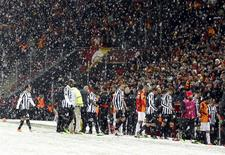 Players of Galatasaray and Juventus walk out of the pitch as their match is paused for 20 minutes due a heavy snowfall during their Champions League soccer match in Istanbul December 10, 2013. REUTERS/Osman Orsal