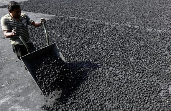 A labourer lays coal balls out to dry at a factory in Kolkata November 4, 2010. REUTERS/Rupak De Chowdhuri/Files