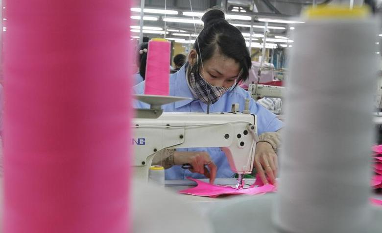 A woman works on the assembly line of a shoe factory in Tan Lap village, outside Hanoi February 22, 2013. REUTERS/Kham