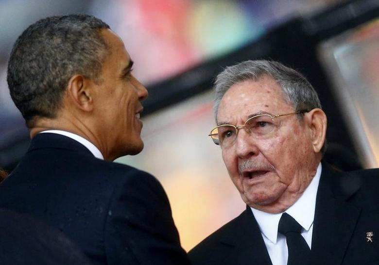 U.S. President Barack Obama (L) greets Cuban President Raul Castro before giving his speech at the memorial service for late South African President Nelson Mandela at the First National Bank soccer stadium, also known as Soccer City, in Johannesburg December 10, 2013. REUTERS/Kai Pfaffenbach