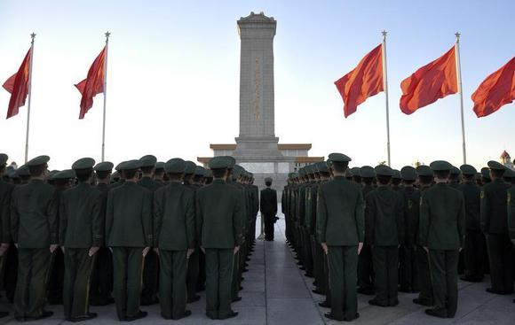 Paramilitary policemen stand in formation as they pay tribute to the Monument to the People's Heroes on Tiananmen Square in Beijing, November 17, 2013. REUTERS/Stringer