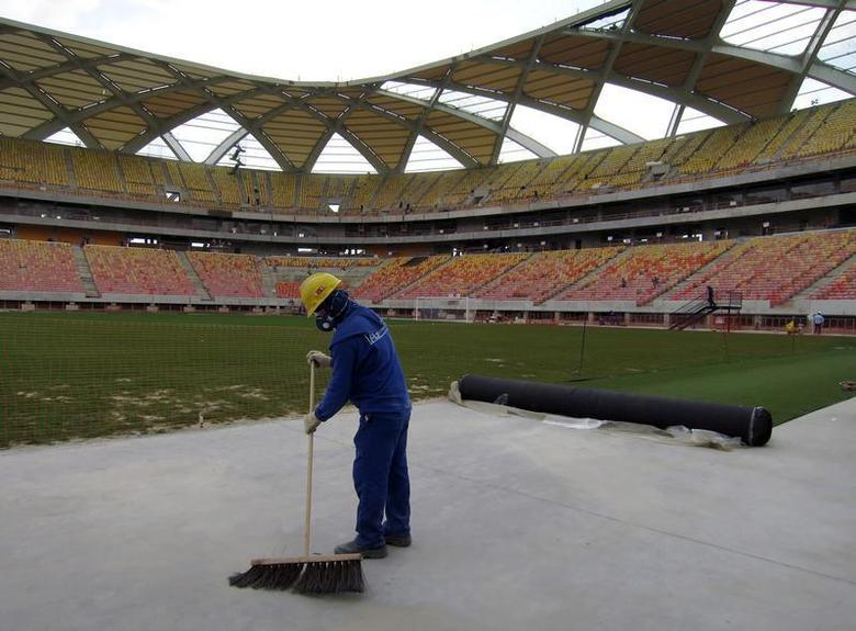 A workman next to the pitch inside the Arena Amazonia stadium as work continues in preparation for the 2014 FIFA World Cup soccer championship in Manaus December 10, 2013. The 2014 World Cup finals will be held in Brazil from June 12 through July 13. REUTERS/Gary Hershorn