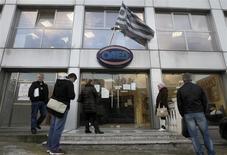 Devant une agence pour l'emploi à Athènes. Le taux de chômage grec est resté proche de son pic historique en septembre, s'établissant à 27,4% de la population active, le marché du travail continuant de subir de plein fouet l'impact de la cure d'austérité que suit le pays depuis plusieurs années. /Photo prise le 11 décembre 2013/REUTERS/John Kolesidis