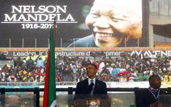 U.S. President Barack Obama gives a speech as a man passing himself off as a sign language interpreter (R) folds his hands during a memorial service for late South African President Nelson Mandela at the FNB soccer stadium in Johannesburg December 10, 2013. REUTERS/Kai Pfaffenbach