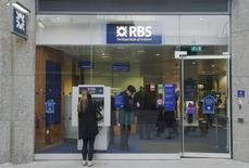 A woman stands in front of a Royal Bank of Scotland (RBS) cash machine, in central London December 3, 2013. REUTERS/Luke MacGregor