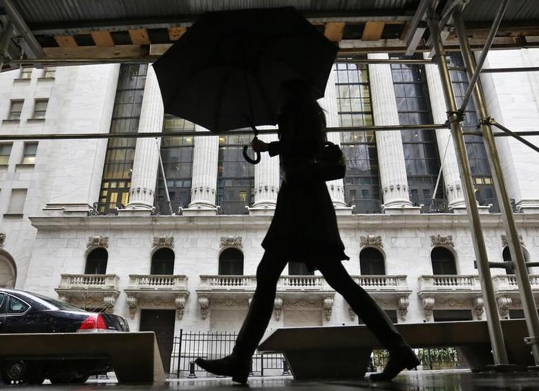 A woman walks past the New York Stock Exchange in New York's financial district, February 8, 2013. REUTERS/Brendan McDermid