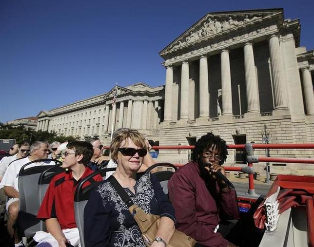 Tourists, with guide Darnell Lacy (R), pass by the closed National Archives building in Washington atop a Big Bus double-decker tour bus. REUTERS/Gary Cameron