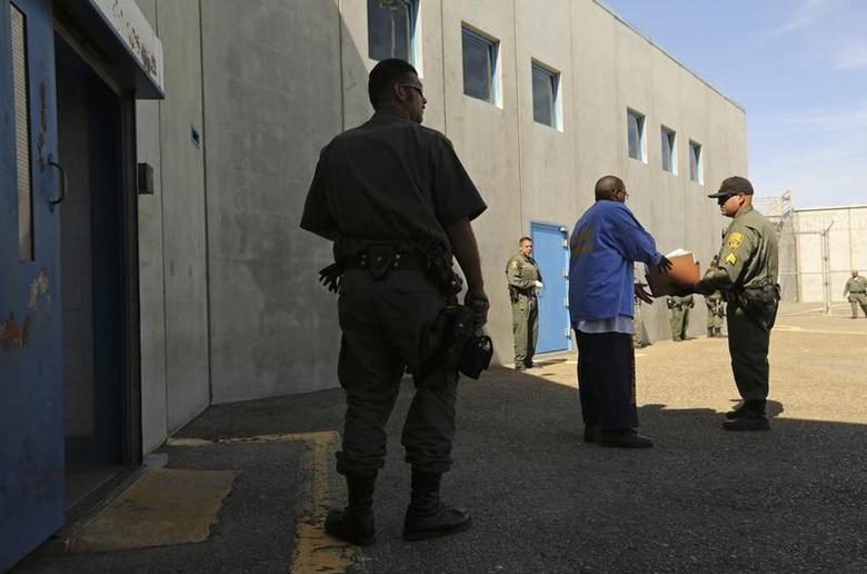An inmate (C) is checked by guards after leaving a general population cell block, in Corcoran State Prison, California October 1, 2013. REUTERS/Robert Galbraith