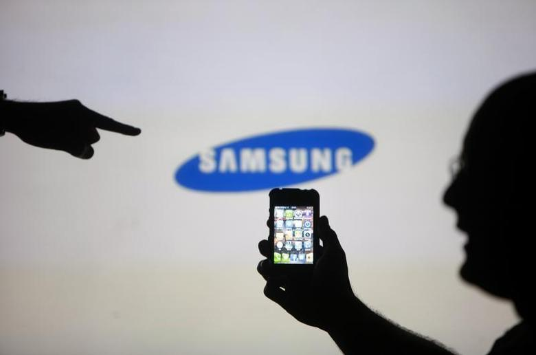 Men are silhouetted against a video screen with an Samsung logo as they pose with an Apple iPhone 4 smartphone in this photo illustration taken in the central Bosnian town of Zenica, May 17, 2013. REUTERS/Dado Ruvic