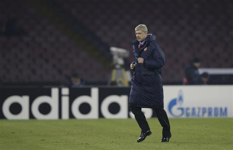 Arsenal's Coach Arsene Wenger leaves the pich at the half-time of the the Champions League soccer match against Naples at San Paolo stadium in Naples, December 11, 2013. REUTERS/Max Rossi