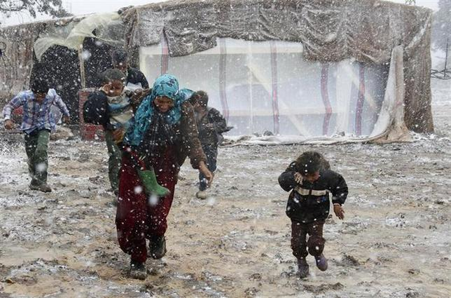 12月11日、シリアの内戦を逃れた家族がテント生活を送るレバノンの難民キャンプに初雪が降った。Zahleで撮影(2013年 ロイター/Mohamed Azakir)