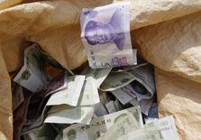 """Пакет торговца с юанями на рынке в Пекине 10 апреля 2013 года. Отток """"грязных"""" денег через незаконные схемы ускорился на 14 процентов и лишил развивающиеся страны почти $1 триллиона в 2011 году, превысив в десять раз объем международной помощи им. REUTERS/Kim Kyung-Hoon"""
