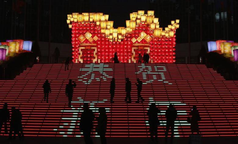 People are silhouetted on an illuminated installation celebrating Chinese Lunar New year at a shopping district in Beijing February 12, 2013. REUTERS/Kim Kyung-Hoon