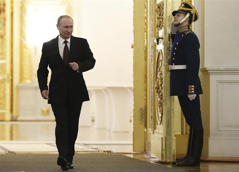 Russia's President Vladimir Putin walks into a room before delivering his annual state of the nation address at the Kremlin in Moscow, December 12, 2013. REUTERS/Dmitry Astakhov/RIA Novosti/Pool