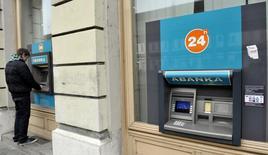 Человек снимает деньги в банкомате Abanka в Любляне 12 декабря 2013 года. Словенским банкам необходимы 4,8 миллиарда евро дополнительного капитала для того, чтобы остаться на плаву, однако власти страны готовы найти эти деньги сами, не прибегая к помощи других стран еврозоны. REUTERS/Srdjan Zivulovic