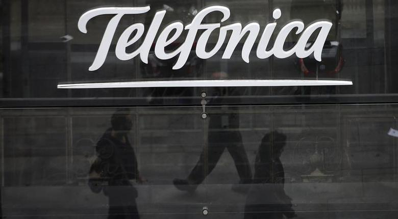 People are reflected as they walk past Spanish telecom group Telefonica's flagship store in central Madrid November 8, 2013. REUTERS/Sergio Perez