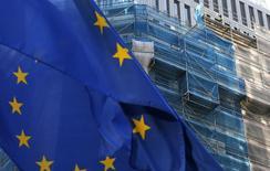 Uma bandeira da União Europeia tremula enquanto um trabalhador é visto em um edifício em reforma em Bruxelas. A União Europeia pediu um adiamento de um mês na troca de propostas para dar início às negociações de livre-comércio com o Mercosul, disse o governo argentino nesta quinta-feira. 09/12/2013 REUTERS/Francois Lenoir
