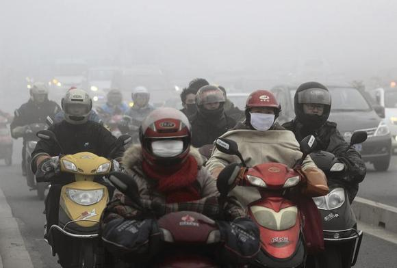Residents wearing masks ride their electric bicycles on a street amid heavy haze in Shaoxing, Zhejiang province December 5, 2013. REUTERS/China Daily