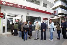 File d'attente devant une banque à Nicosie lors de l'annonce du plan de sauvetage de Chypre qui nécessitait la confiscation d'une partie de l'épargne des plus gros déposants. Selon le ministre chypriote des Finances Haris Georgiades, le pays a évité un effondrement de son économie et le plan d'austérité élaboré et supervisé par ses créanciers internationaux commence à porter ses fruits. /Photo prise le 29 mars 2013/REUTERS/Bogdan Cristel