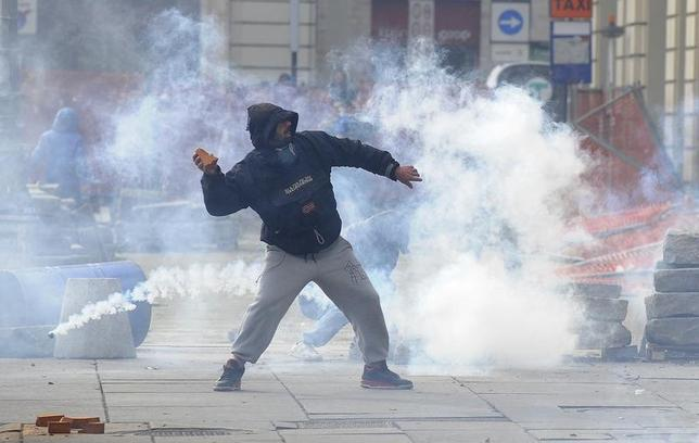 A protester throws a stone during a protest in downtown Turin December 9, 2013. REUTERS/Stringer