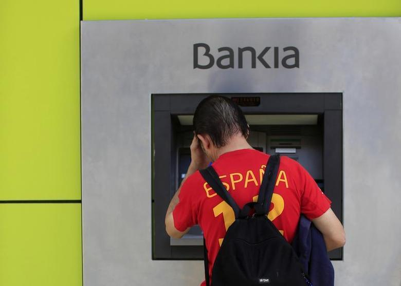 A man uses an ATM machine at a Bankia bank branch in the Andalusian capital of Seville, southern Spain October 28, 2013. REUTERS/Marcelo del Pozo