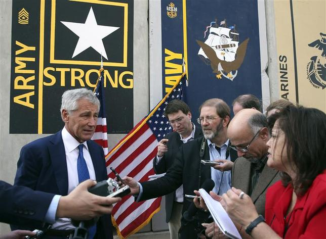 U.S. Secretary of Defense Chuck Hagel (L) speaks to reporters at the Al Udeid Airbase, west of Doha December 10, 2013. REUTERS/Mark Wilson/Pool