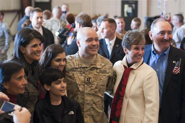 U.S. Army Captain Michael Haley and First Gentleman of South Carolina, is pictured with his wife South Carolina Governor Nikki Haley (2nd L) and his family upon arriving at an an airport in Columbia, South Carolina, December 12, 2013, in this handout photo courtesy of the South Carolina Army National Guard. The husband of South Carolina Governor Nikki Haley has returned home from an 11-month deployment with the U.S. National Guard in Afghanistan where he trained farmers to grow crops other than poppies, which are used to make heroin. REUTERS/South Carolina Army National Guard/Tech. Sgt. Jorge Intriago/Handout via Reuters