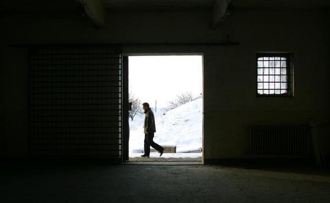 A Romanian journalist walks past a building inside the Mihail Kogalniceanu Airbase, east of Bucharest, December 19, 2005. The airbase was indicated by Human Rights Watch as a possible location for a covert prison allegedly used by the CIA in Romania to interrogate terrorist suspects. REUTERS/Bogdan Cristel