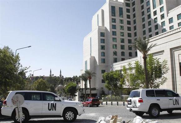 United Nations (U.N.) vehicles are parked in front of the Four Seasons hotel, where a team of experts from the Organisation for the Prohibition of Chemical Weapons (OPCW) are staying, in downtown Damascus October 22, 2013. REUTERS/Khaled al-Hariri/Files