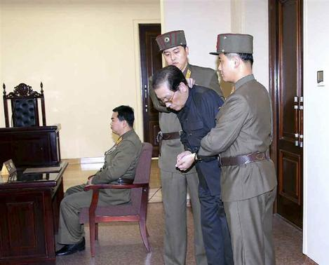 Jang Song Thaek, with his hands tied with a rope, is dragged into the court by uniformed personnel in this December 13, 2013 picture taken from Rodong Sinmun December 12, 2013 and released by Yonhap. REUTERS-Yonhap