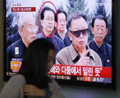 A woman walks past a television showing a report on Jang Song Thaek (circled) at a railway station in Seoul in this December 3, 2013 file photo. REUTERS-Kim Hong-Ji-Files