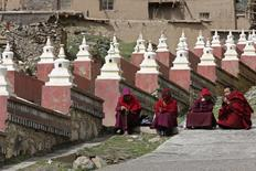 Tibetan monks sit at an entrance to the Dzamthang Jonang monastery, where Tibetan woman Kalkyi set herself on fire in protest against Chinese rule, in Barma township May 16, 2013. REUTERS/Kim Kyung-Hoon