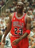 """Une paire de baskets portées et signées par Michael Jordan lors d'un match de la finale NBA de 1997 a été vendue aux enchères pour la somme record de 104.765 dollars (76.000 euros). Le numéro 23 des Chicago Bulls portait ces chaussures rouge et noir lors du cinquième match de la finale contre les Utah Jazz, le 11 juin 1997, surnommé le """"match de la grippe"""" (""""flu game"""") parce qu'il jouait diminué par le virus. /Photo prise le 11 juin 1997/REUTERS"""