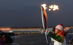 A runner carries the Sochi 2014 Winter Olympic torch along a bridge across Yenisei River near the Krasnoyarsk hydro electric power station near the town of Divnogorsk outside Krasnoyarsk, November 25, 2013. REUTERS/Ilya Naymushin