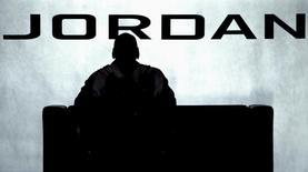 Майкл Джордан смотрит баскетбольный матч в Гонконге 21 мая 2004 года. Пара кроссовок, которую легенда баскетбола Майкл Джордан надевал во время знаменитой игры финальной серии НБА 1997 года, ушла с молотка за рекордные $104.765. REUTERS/Bobby Yip