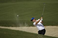 Justin Rose of England hits the ball out of the bunker approaching the second hole during the third round of the DP World Tour Championship in Dubai November 16, 2013. REUTERS/Caren Firouz