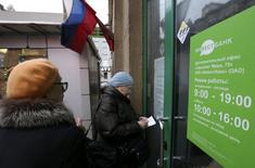 Женщины стоят у двери отделения Инвестбанка в Москве 13 декабря 2013 года. Центробанк РФ отозвал лицензии у Банка проектного финансирования, банка Смоленский и Инвестбанка: все три вели высокорискованную кредитную политику, которая стала причиной проблем с ликвидностью, сообщил ЦБ в пятницу. REUTERS/Sergei Karpukhin