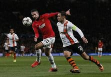 Manchester United's Robin Van Persie (L) is challenged by Shakhtar Donetsk's Darijo Srna during their Champions League soccer match at Old Trafford in Manchester, northern England December 10, 2013. REUTERS/Phil Noble