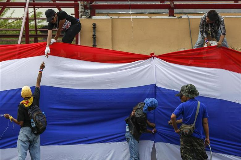 Anti-government protesters place a large Thai national flag on the gate and fence around Government House in Bangkok December 13, 2013. REUTERS/Athit Perawongmetha