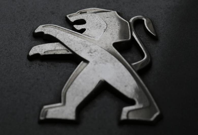 A company logo is seen on a Peugeot car parked in Paris, February 12, 2013. REUTERS/Christian Hartmann