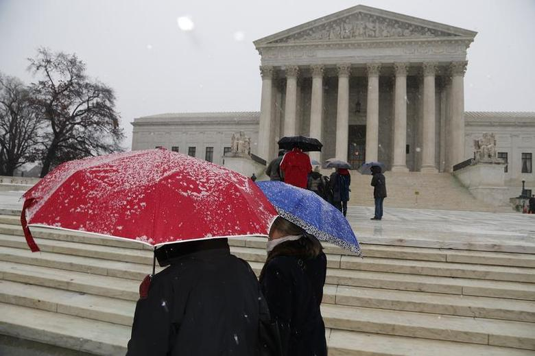 A light snow falls as visitors gather on the steps of the U.S. Supreme Court in Washington, December 10, 2013. REUTERS/Jonathan Ernst