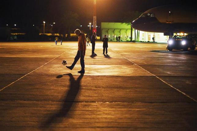 U.S. Secretary of State John Kerry dribbles a soccer ball on the tarmac at the airport in Aqaba, during a refueling stop, December 13, 2013. REUTERS/Brian Snyder