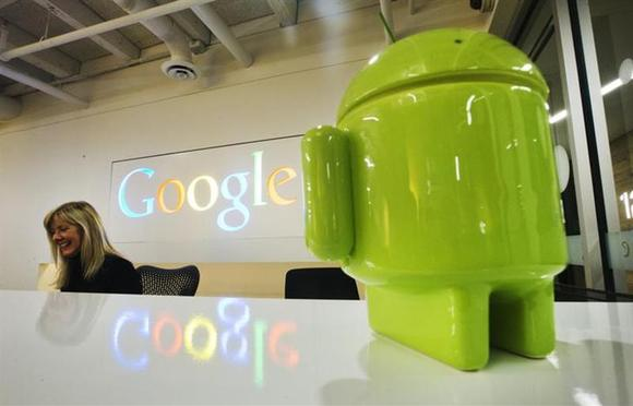 A Google Android figurine sits on the welcome desk as employee Tracy McNeilly smiles at the Google office in Toronto, November 13, 2012. REUTERS/Mark Blinch/Files