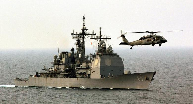 A helicopter hovers over the Ticonderoga-class guided missile cruiser USS Cowpens in the northern Gulf March 12, 2003. REUTERS/Paul Hanna