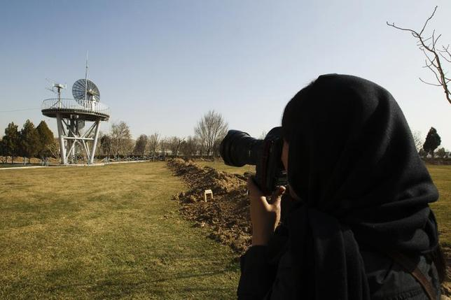 A photojournalist takes pictures at the Iranian Space Agency (ISA) in Mahdasht, about 60 km (37 miles) west of Tehran, February 29, 2012. REUTERS/Raheb Homavandi