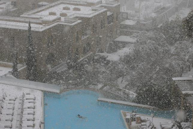 A woman swims in the pool at the David Citadel Hotel during a snow storm in Jerusalem December 13, 2013. REUTERS/Brian Snyder